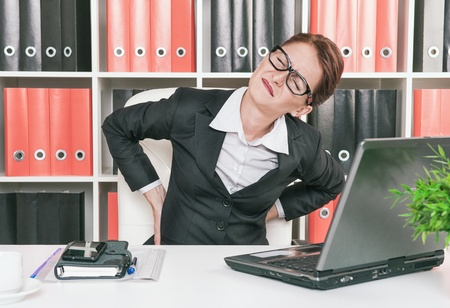 Business woman with pain in her back working at office photo
