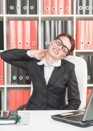 Business woman with pain in her neck working at office photo