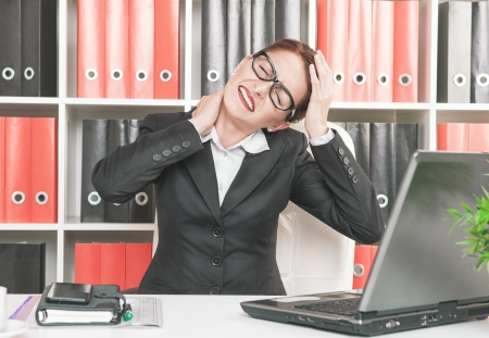 Business woman with pain in her neck and head working at office