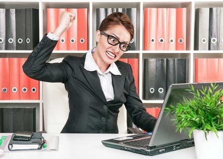 Angry screaming business wants to break computer with her fist photo