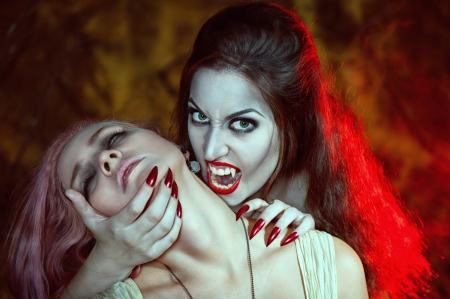 Beautiful vampire woman and her victim  photo