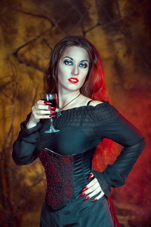 Beautiful halloween woman with long hair and glass of wine photo