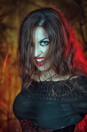 Beautiful angry halloween witch with long hair photo