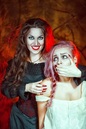 Beautiful smiling halloween witch and her victim photo