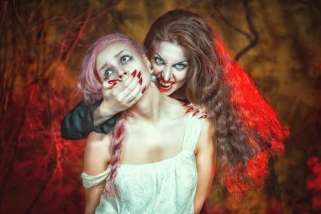 Halloween beautiful vampire and her victim Stock Photo