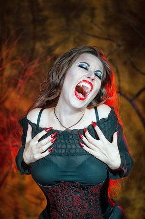 Screaming halloween beautiful vampire with long hair photo