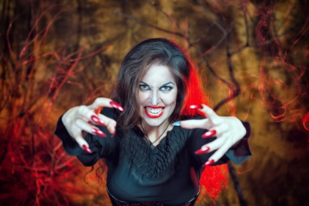 Beautiful angry halloween witch with long nails photo