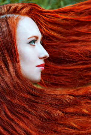 Portrait of redhead young woman with long hair photo