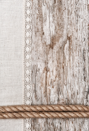Linen fabric with lace and rope on the old rustic wooden background photo