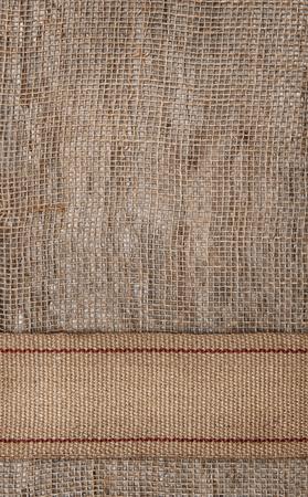 Burlap textile background with sacking ribbon photo