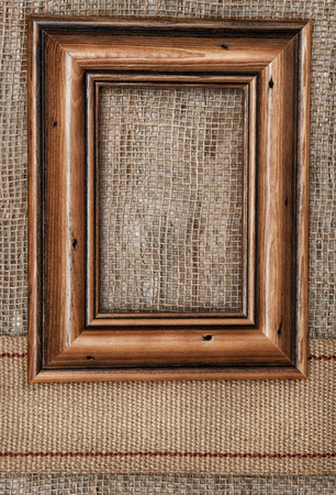 Wooden frame on the burlap textile background with sacking ribbon photo