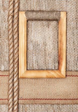 Wooden frame on the burlap textile background with sacking ribbon and rope photo