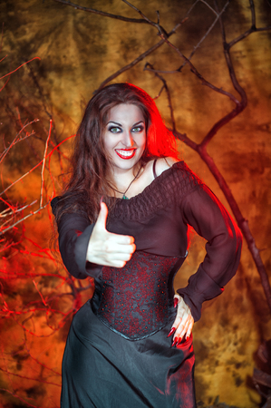 Beautiful smiling halloween witch showing  thumbs up photo