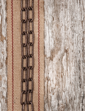 Metal chain and hardware burlap ribbon on the old wood photo