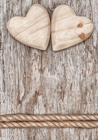 Two wooden hearts and rope on the old wood background Foto de archivo