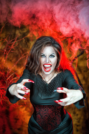 Angry halloween beautiful vampire with long nails holding out hands photo
