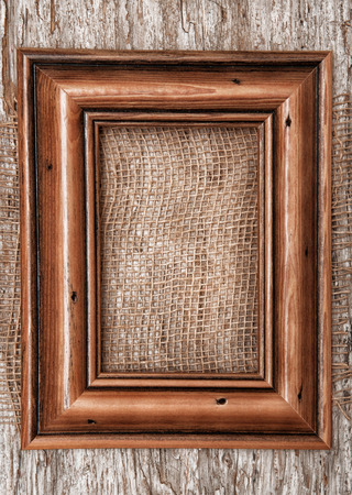 Wooden frame and burlap textile on the old wood background photo