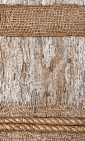 Rope and burlap textile on the old wood background photo