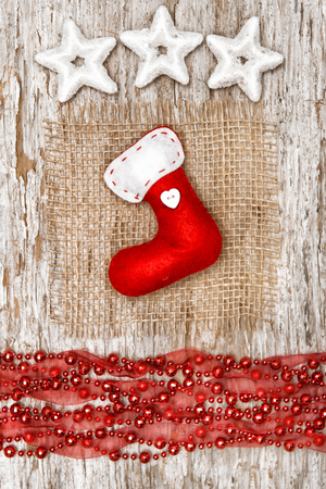Red sock with garland and star shapes on the old wood background photo