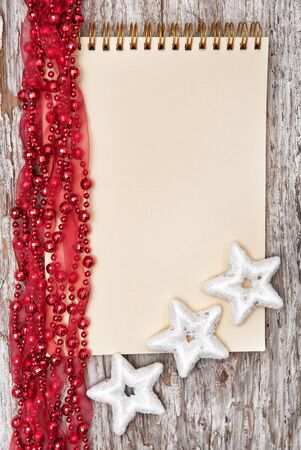 Christmas background with notebook, silver stars and red garland photo