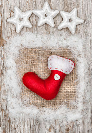 Christmas red sock with snow on burlap textile and old wood background photo