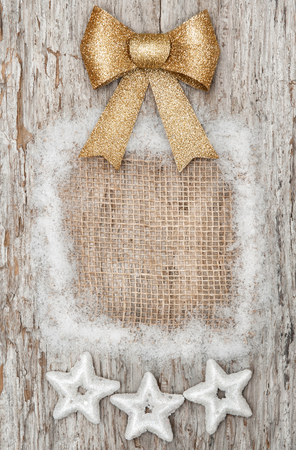 Christmas decoration with golden bow and silver stars on the old wood background photo