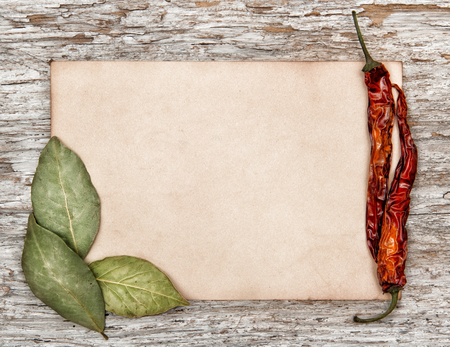 Aged sheet of paper with dry bay leaves and pepper on the old wooden background photo