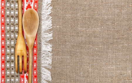 Burlap background bordered by red and green country cloth and utensils photo
