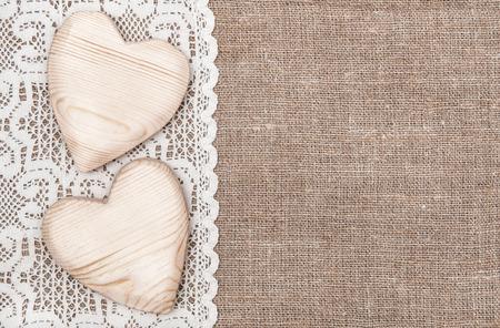 Fondo de arpillera con el paño blanco de encaje y corazones de madera Foto de archivo - 23879983