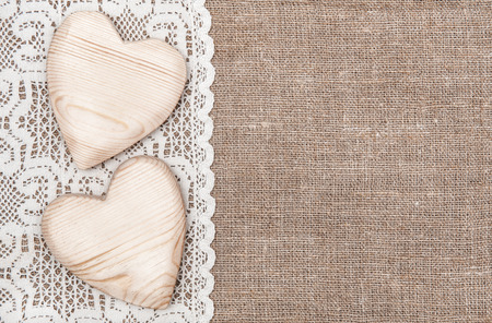 Jute achtergrond met witte kanten doek en houten harten Stockfoto