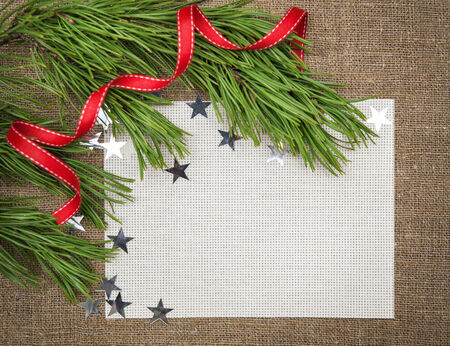 Christmas card with fir branch, stars and red ribbon on burlap background photo