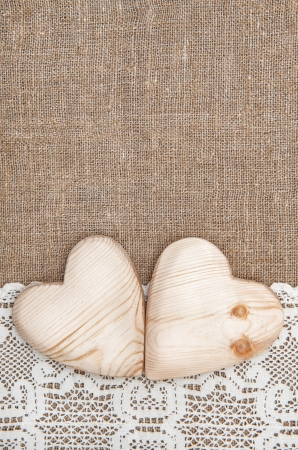 hessian: Burlap background with white lacy cloth and wooden hearts