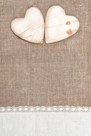 Burlap background with white lacy cloth and wooden hearts