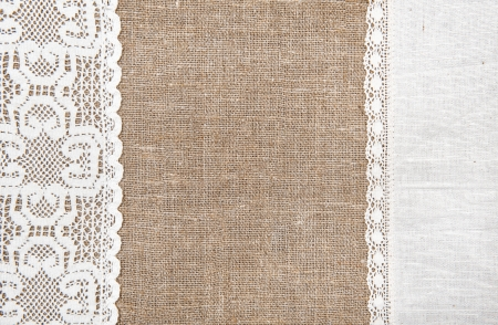Burlap background with white lacy and linen cloth photo