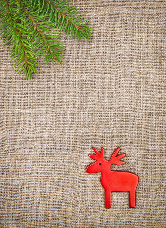 Christmas decoration with fir branch and red deer on burlap background photo