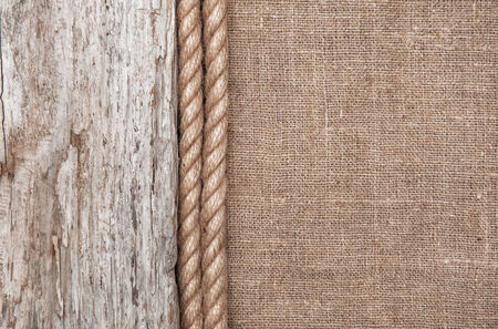 Burlap background bordered by rope and rude old wood photo