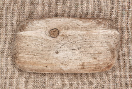 Piece of old wood on textile burlap background  photo