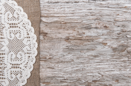 sackcloth: Old wood bordered by lacy cloth and burlap background Stock Photo