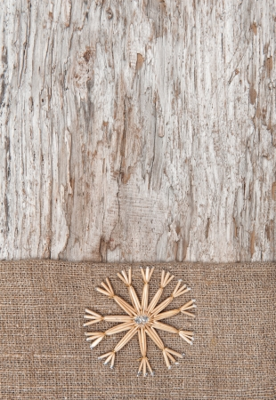 Christmas decoration with straw snowflake and burlap on old wood background photo