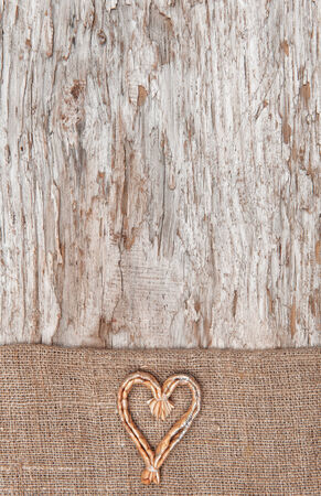 Christmas decoration with straw heart and burlap on old wood background photo