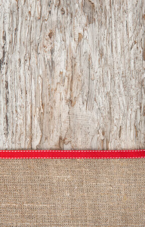 Old wood bordered by burlap background and red ribbon photo
