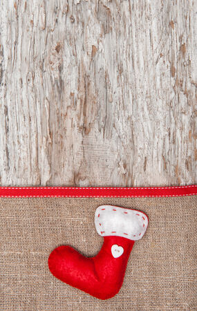 Christmas decoration with red sock and burlap on old wood background photo