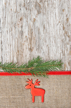 Christmas decoration with red deer and burlap on old wood background photo