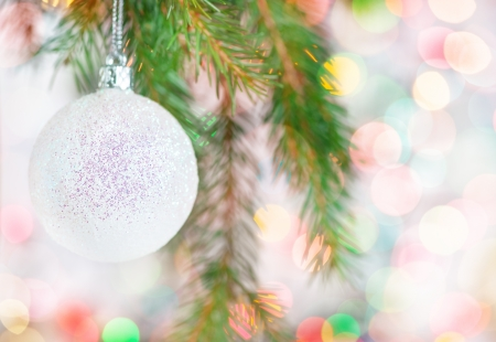 Abstract bokeh background with christmas ball on fir tree photo