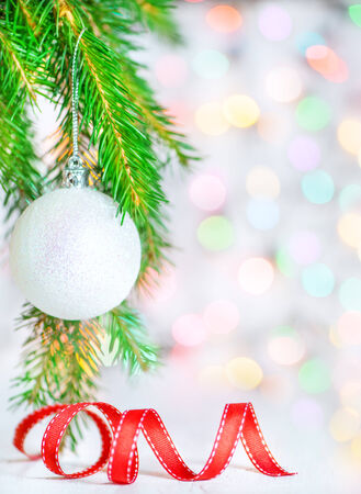 Christmas ball and red ribbon on abstract bokeh background photo