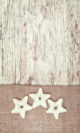 Christmas decoration with silver stars and burlap on old wood background
