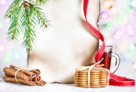 Christmas card with tea, cookies, cinnamon and abstract bokeh background photo