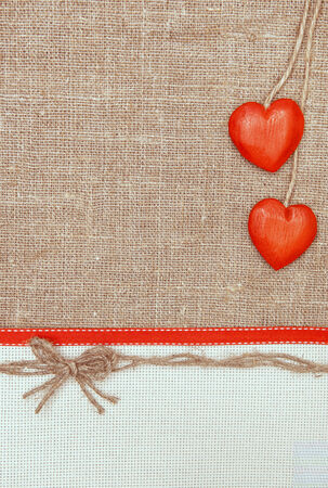 Valentine card with red hearts and ribbon on burlap  photo