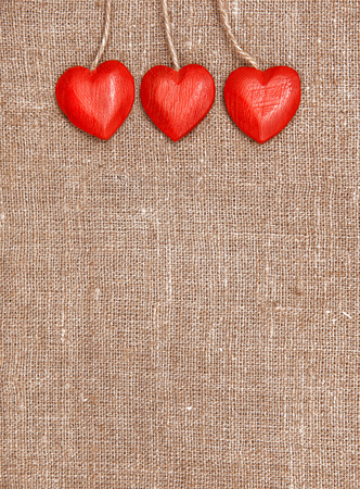 Wooden red hearts on hessian  photo