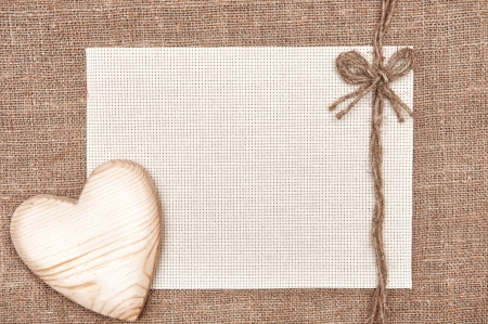 Valentine card with wooden heart and canvas on burlap  Stock Photo